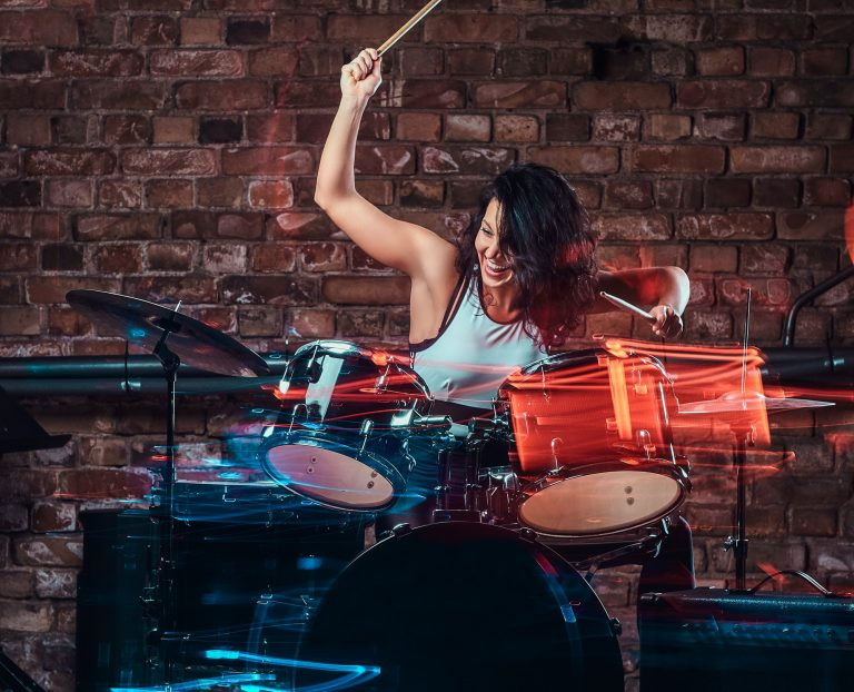 Young girl musician playing on drums and cymbals. Live music in a night club